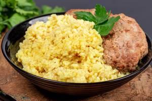Schwarzer Teller mit Weizen-Porridge, frischer Petersilie und Hackbraten auf einem Holzschneidebrett Nahaufnahme