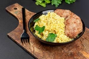 Schwarzer Teller mit Weizen Porridge, frischer Petersilie und Hackbraten mit Gabel auf einem Holzschneidebrett