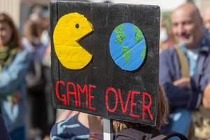 Schwarzes Demonstrationsschild mit Pac-man frisst die Welt Symbolik