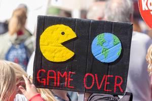 """Schwarzes Demonstrationsschild zeigt Pac-man frisst die Welt bildlich mit der Unterschrift """"Game Over"""""""