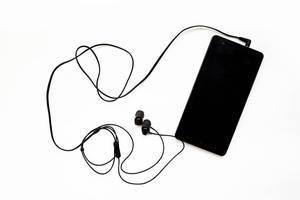 Schwarzes Smartphone mit angeschlossenen In-Ear-Kopfhörern vor weißem Hintergrund