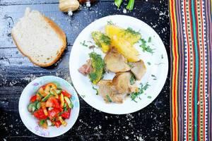 Schweinebraten mit Brot und gemischtem Gemüsesalat auf einem schwarzen Hintergrund