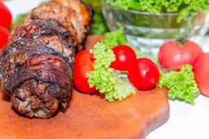 Schweinebraten-Roulade mit Tomaten auf Holzbrett und grünem Salat in Glasschale
