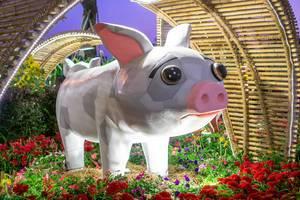 Schweinefigur mit traurigem Blick auf Blumen unter Bambusbogen in Ho Chi Minh City, Vietnam