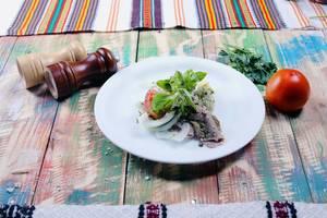 Schweinefleisch mit Tomate, Salz und Pfeffer auf einem hölzernen Tisch