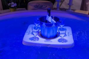 Schwimmende Insel mit Champagnerkühler und vier Gläsern in Whirlpool in blauem Licht