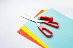 Scissors and glue laying on stacked colorful craft paper on white background