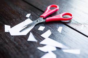 Scissors laying on wooden table with small pieces of paper