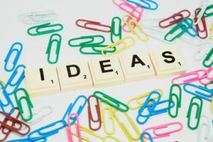 """Scrabble - Spielsteine zeigen das Wort """"Ideas"""", inmitten bunter Büroklammern"""