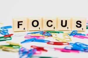 """Scrabble Steine bilden das Wort """"Focus"""" Fokus, hinter bunten Büroklammern"""