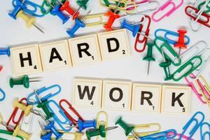 """Scrabble-Steine legen das Wort """"Hard Work"""" - Harte Arbeit, zwischen bunten Reißzwecken und Büroklammern"""