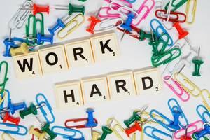 """Scrabble Steine zeigen den Text """"Work Hard"""" - Arbeite hart - mit Reißzwecken und bunten Büroklammern auf weißem Untergrund"""