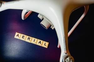 """Scrabblespielsteine zeigen das englische Wort """"Aerial"""" für Luft, neben einer Drohne für Luftaufnahmen"""