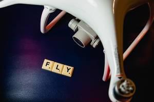"""Scrabblespielsteine zeigen das englische Wort """"Fly"""" für Flug/fliegen, auf blauem Untergrund, neben einer weißen Drohne"""