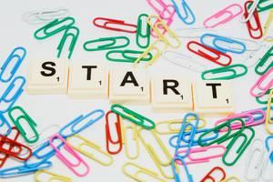 Scrabblesteine bilden das Wort Start, umgeben von bunten Büroklammern