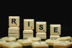 """Scrabblesteine ergeben das Wort ansteigen/erheben """"Rise"""", vor einem schwarzen Hintergrund"""