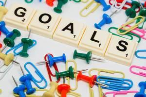 Scrabblesteine legen das Wort Goals zwischen Bürobedarf-Utensilien