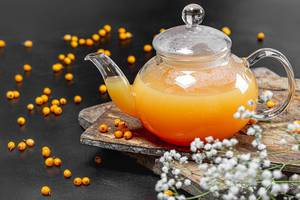 Sea buckthorn hot drink in a teapot with fresh berries on a black background
