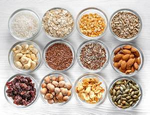 Seeds, nuts, grains in glass bowls on a white wooden background. Top view (Flip 2019)