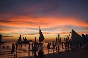 Segelboote legen im Sonnenuntergang zur goldenen Stunde am Strand von Boracay an