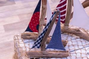 Segelbote hergestellt aus Ästen und Schnüren mit kleinen Stoffsegeln auf Holzkiste mit Fischernetz