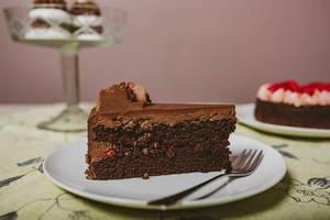 Seitenansicht auf ein Stück saftigen Schokoladentorte, als Nachspeise angerichtet auf einem weißen Teller