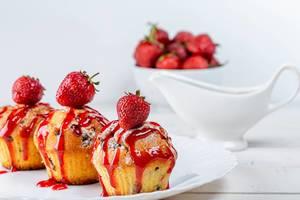 Selbstgebackene Muffins mit Erdbeersauce und frischen Beeren verziert, auf einem weißen Teller