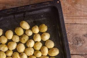 Selbstgemachte frische Biokartoffeln mit Kräutern auf einem schwarzen Backblech