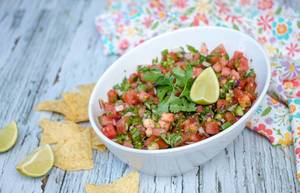 Selbstgemachte Salsa, mit Minze, Limette und Tomaten, neben Nachos auf einem rustikalen, alten Küchentisch