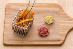 Selbstgemachte Süßkartoffel-Pommes mit Ketchup und Senf in Servier-Friteuse