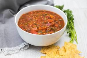 Selbstgemachte Tomaten-Salsa zu Nachos neben Petersilie und Serviette
