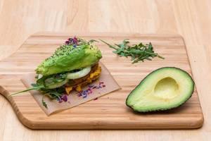 Selbstgemachter Avocado-Burger mit Sesam, Kräutern, Zwiebeln, Humus und Veggie-Frikadelle