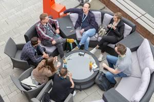 Selbstständige und Teilnehmer des Barcamp OMWest19 von AXA in Köln, machen eine Pause auf runden Rattanmöbeln auf einer Terasse