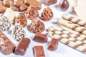 Selektion von Pralinen, Keksen, Schokolade-Süßigkeiten und Waffeln vor weißem Hintergrund