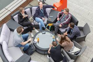 Self-employed and participants of the Barcamp OMWest19 of AXA in Cologne, taking a break and talking on round rattan furniture on a terrace