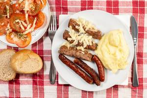 Served meal with Kebabs Sausages Mashed Potatoes and Tomatoes