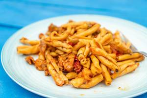 Served-Pasta-with-Tuna-on-the-white-plate-above-blue-wooden-table.jpg
