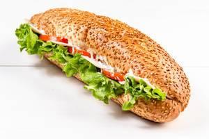 Sesambrot-Sandwich mit Salat, Tomaten, Schinken und Käse auf weißem Tisch