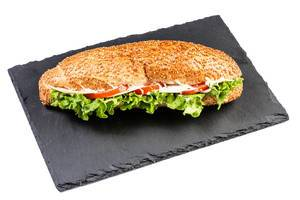 Sesambrötchen-Sandwich belegt mit Salatblätter, Schinken, Tomaten und weißer Sauce auf schwarzer Schieferplatte
