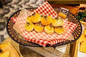 Sesame rolls on wooden basket with table cloth