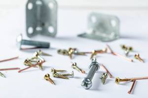 Set aus verschiedenen Schrauben, Nägeln und Bolzen assortiert auf weißem Hintergrund