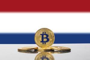 Set aus vier Bitcoins in gold vor der niederländischen Flagge