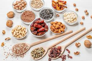 Set nuts, seeds, dried fruits in different bowls and wooden spoons on white wooden background (Flip 2019)