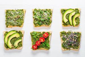 Set of different sandwich with herbs, micro greens, vegetables and seeds on white wooden background. Top view (Flip 2019)