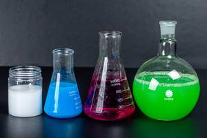 Set of laboratory glassware with chemical multi-colored solutions on a black background (Flip 2020)