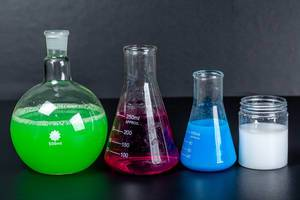 Set of laboratory glassware with chemical multi-colored solutions on a black background