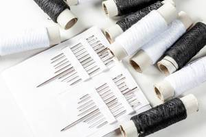 Set of needles of different sizes with black and white threads