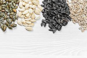 Set of sunflower seeds and pumpkin on white wooden background