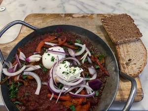 Shakshuka: eine dampfend heisse, Nordafrikanische Schmorpfanne mit Tomaten, frischer Paprika, roten Zwiebeln, zwei Eiern und geröstetem Brot