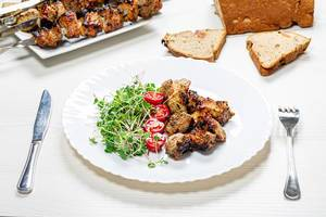 Shashlik with micro greens radish and tomato slices on a white wooden table with a knife and fork (Flip 2019)